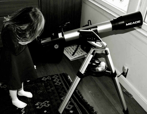 Toddler in dress peering through telescope