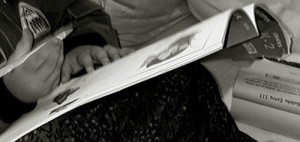 Young toddler hands holding pen and workbook